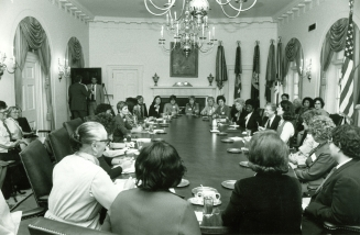 Erma Bombeck at a meeting of President Carter's National Advisory Committee for Women. President Carter is seated in the middle on the left side of the table. Erma is at the far head of the table. October 23, 1979