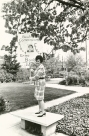 Erma Bombeck holds her commissioner sign while standing on a bench.